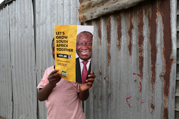A young girl holds an election poster of the ruling African National Congress (ANC) during President Cyril Ramaphosa's visit to Khayelitsha township near Cape Town