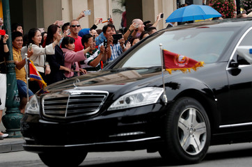 Bystanders take photos of North Korean leader Kim Jong Un's motorcade as it leaves the Metropole after the North Korea-U.S. summit in Hanoi