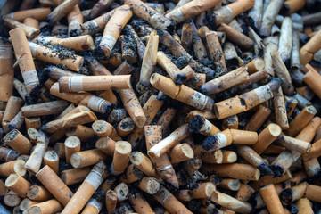 Cigarette butts background. Closeup of ashtray