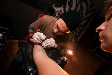 A man master fills a tattoo to a young man. Tattoo parlor. Drawing on skin. Lifestyle