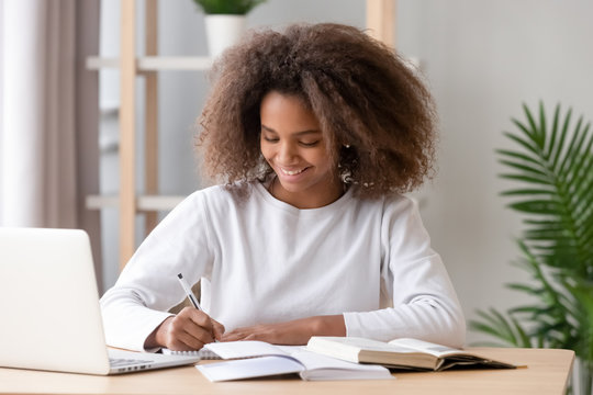 Positive african schoolgirl sitting at desk and study