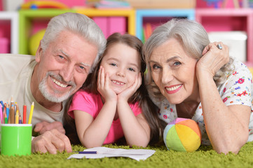 Portrait of grandparents playing with grandaughter while lying on floor