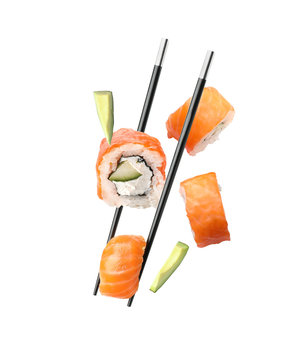 Tasty sushi rolls, chopsticks and avocado on white background