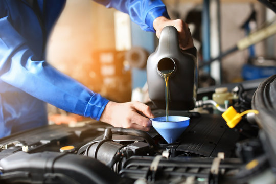 Male mechanic refilling car oil in service center