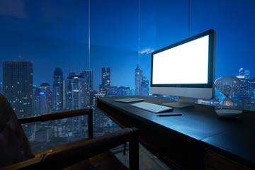 Computer on desktop with Bangkok city skyline view in dusk.
