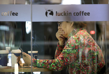 The logo is seen next to a customer at a Luckin Coffee store in Beijing