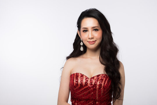 Portrait of Miss Pageant Beauty Contest in Red sequin Evening Ball Gown long dress with sparkle light Diamond Crown, Asian Woman fashion make up black hair style, studio lighting white background