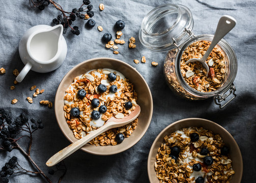 Homemade granola with greek yogurt and blueberries on a grey background, top view. Healthy energy breakfast or snack. Flat lay