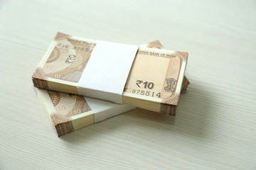 New Indian Currency Rupees from pack. Isolated on wooden background.