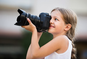 Girl taking pictures with professional camera outdoors