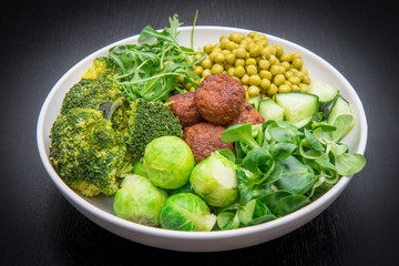 vegan dish with soy meatballs and green vegetables