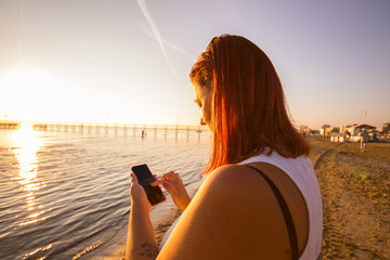 beautiful woman  write on smartphone on the beach on sunset