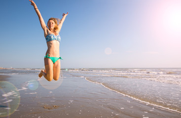 beautiful woman jump on the beach in the sea