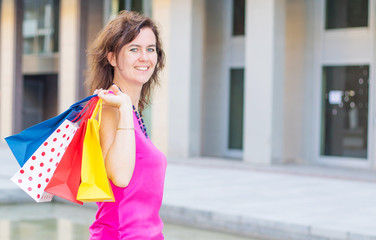 smiling woman with colored shopping bag