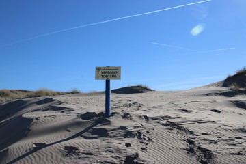 Sign with dutch text Verboden toegang which means in English no admittance of the water authority Delfland in the dunes of Monster in the Netherlands