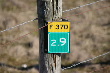 Distance sign in kilometers on the cycle route F370 at the coast of Monster