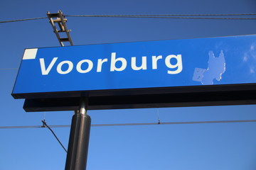 Blue and white name sign Voorburg on the platform of the railway station in the Netherlands