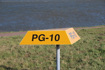 Yellow triangle warning signs above underground pipeline with tag number on it in the port of Rotterdam, the Netherland