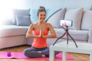 Portrait of a beautiful young yoga instructor recording a video for her blog at home