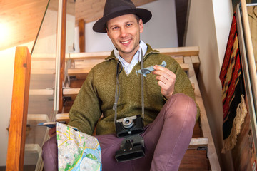 Hipster young man traveler  holing up a map and a plane , take a pictures by old camera