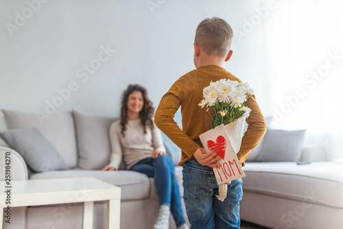 Happy mother's day! Child son congratulates mom and gives her postcard. Mum and boy smiling and hugging. Family holiday and togetherness.