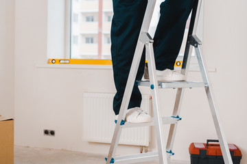 cropped view of man standing on ladder in room