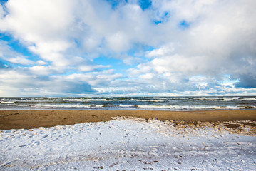 Snow-covered seacoast on a sunny winter day. Cold stormy waves and clouds over the North sea, Netherlands