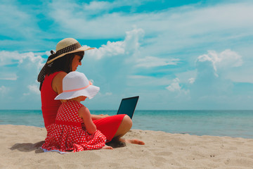 mother and little daughter looking at laptop on beach