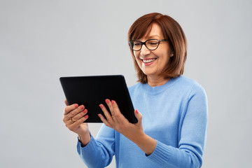 technology and old people concept - smiling senior woman in glasses using tablet computer over grey background