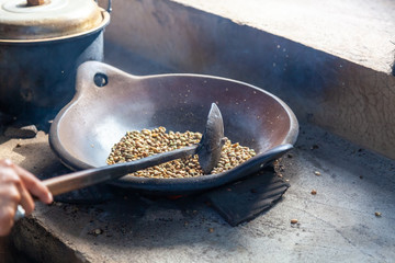 Person roasting fresh coffee beans in a skillet