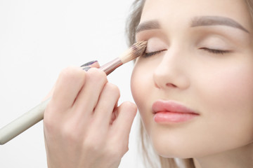 Make-up artist makes makeup beautiful blonde girl on a white background. Close-up hands with brush and face.