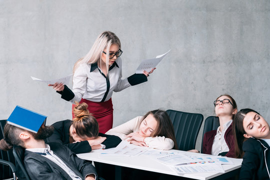 Business meeting failure. Overworking stress. Astounded executive woman looking at sleeping employees. Copy space on grey background.