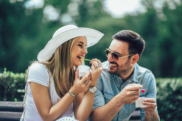 Couple joking and having fun while eating an ice cream in the park.