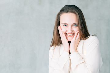 Young smiling woman portrait. Successful job interview. Career start. Copy space on grey background.