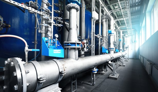 New shiny pipes, large pumps in industrial boiler room, close-up. Industry, technology, special equipment, water treatment, pure drinking water, biotechnology, chemistry, ecology, environmental damage