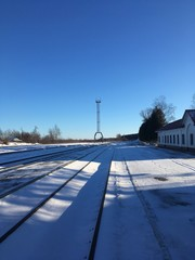 Railway station platform in winterday with ultramarine shadows. Landscape - architecture. Russian trip. Russia and Europe. Winter architecture. Beautiful metal tower. Tula — travel. Snow railway road.