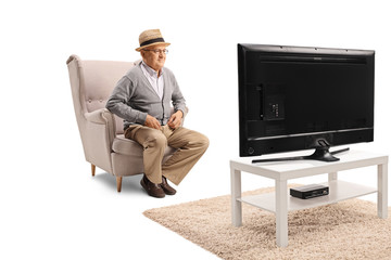 Senior man sitting in an armchair and watching television