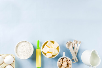 Baking ingredients and tools on trendy bright blue background - flour, eggs, sugar, milk, butter, layout, flatlay top view copy space banner