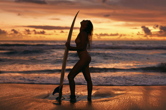 Surfer girl with surf board on sunset beach on summer vacation