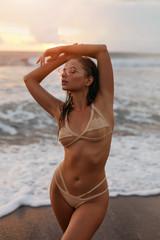 Woman in fashion swimsuit on sea beach in summer