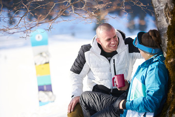 young couple resting while drinking tea on a snowy mountain after skiing