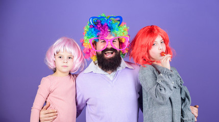 Just for fun. Party time. How crazy is your father. Man bearded father and kids girls wear colorful wig violet background. Friendly family wear party accessories. Best dad ever. Father hug daughters