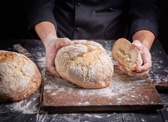 cook in a black tunic holds fresh baked bread
