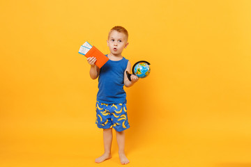 Wall Mural - Kid boy 3-4 years old in blue beach summer clothes hold globe passport isolated on bright yellow orange wall background children studio portrait. People childhood lifestyle concept Mock up copy space.
