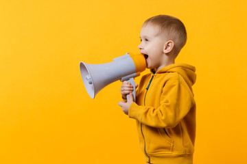 Little fun kid boy 3-4 years old in yellow clothes holding, speaking in electronic megaphone isolated on orange wall background, children studio portrait. People childhood concept. Mock up copy space. Wall mural