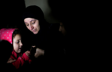 Mother and sister of Palestinian teenager Mohammad Ayoub look at his picture on a mobile phone at their house in Gaza City