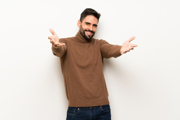 Handsome man over white wall presenting and inviting to come with hand