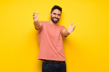 Handsome man over yellow wall presenting and inviting to come with hand