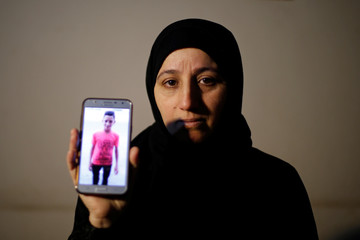 Mother of Palestinian teenager Mohammad Ayoub, who was killed during a protest at the Israel-Gaza border fence, shows his picture on a mobile phone at her house in Gaza