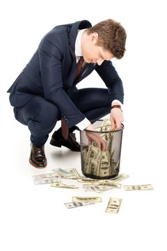 young businessman taking money from trash can on white